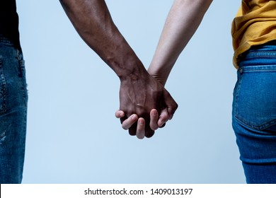 Multiracial couple holding hands together in love. White and black skin arms holding together. Conceptual image of world unity interracial love and understanding in tolerance and diversity.