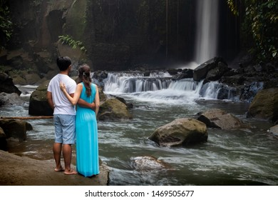 Multiracial couple hugging near waterfall in tropical forest. Young mixed race couple on vacation in Asia. View from back. Romantic relationship. Love story. Sumampan waterfall, Ubud, Bali, Indonesia