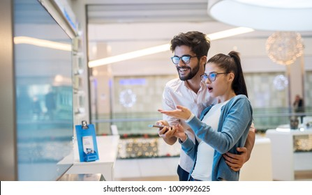 Multiracial couple looking at large TV screen at tech store. Buying 3D TV for living room. Multiethnic couple at shopping.
