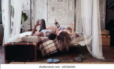 Multiracial couple lying on bed, listening music on smartphone. Man and woman in pajamas spending morning together.