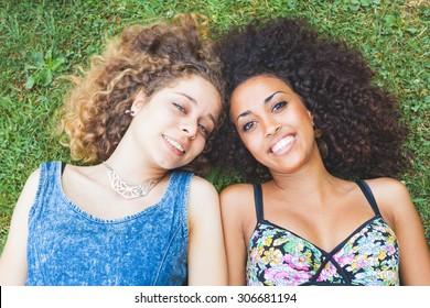 Multiracial couple lying on the grass. They are two young women resting at park. One is caucasian and the other is black, both have curly hair. They are smiling and wearing summer clothes.