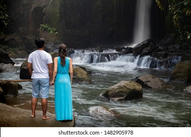 Multiracial couple near waterfall in tropical forest. Young mixed race couple on vacation in Asia. View from back. Romantic relationship. Love story. Sumampan waterfall, Ubud, Bali, Indonesia