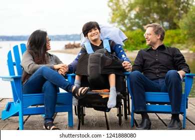 Multiracial couple sitting with disabled twelve year old son in wheelchair while sitting in blue adirondack chairs on wooden pier by lake on summer day
