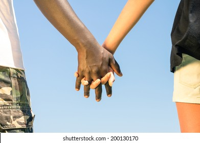 Multiracial couple walking hand in hand against a blue sky - Concept of multi ethnic love over social barriers