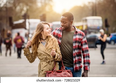 Multiracial couple walking in London. He is middle eastern, she is caucasian, both are smiling and looking each other. They could be friends or in a relationship. Lifestyle and love concepts.