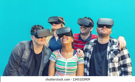 Multiracial diverse group of friends playing on vr glasses indoor - Virtual reality concept with young people having fun together connecting with headset goggles. Digital generation trends
