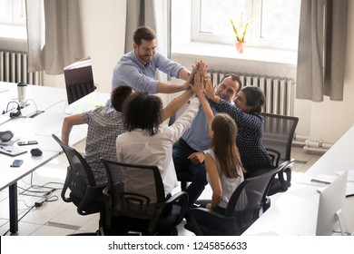 Multiracial employees team with male leader, coach giving high five at company meeting, boss with office workers celebrating business achievement, corporate success of teamwork, team building activity