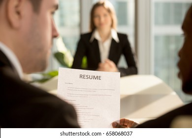 Multiracial employers making hiring decision to fill a vacancy while female job applicant waiting for result at background, recruiters considering candidate holding cv at interview, focus on resume