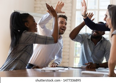 Multiracial euphoric business team people give high five at office table, happy excited diverse work group engaged in teambuilding celebrate corporate success win partnership power teamwork concept