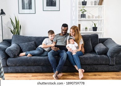 A multiracial family relaxing with a digital tablet sitting on the comfortable sofa, watching video, playing game on the touchscreen, have fun together. Spouses, baby girl and school-age son