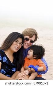 Multiracial family sitting on beach on misty, foggy day.