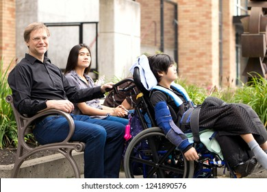 Multiracial family with special needs child sitting outdoors together on summer day. Child is sitting in wheelchair.