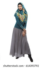 Multiracial female wearing a stylish green hijab mostly associated with middle east, islamic, and eastern european cultures.  The image depicts conservative modern fashion.