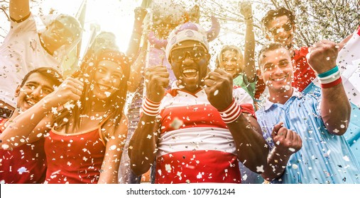 Multiracial football supporters celebrating begin of world competition - Happy multiracial people having fun together outside of stadium - Main focus on black man face - Sport and bonding concept