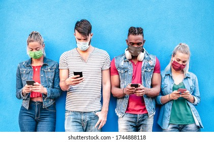 Multiracial friends with face masks using tracking app with mobile smart phones - Young milenial people watching content on social media networks - New normal lifestyle concept - Bright vivid filter