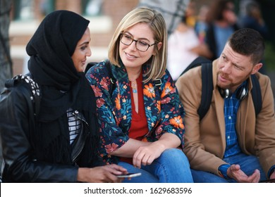 Multiracial friends hanging out sitting on bench in city chatting