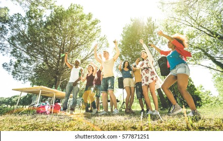 Multiracial friends having fun at barbecue pic nic garden party - Friendship multicultural concept with young happy people drinking and dancing out at spring break camp - Sunshine halo greenery filter