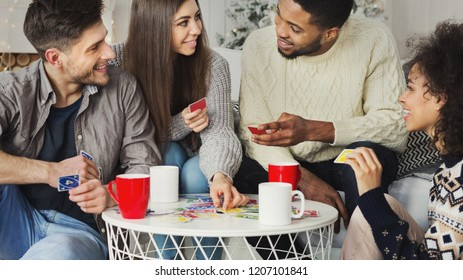 Multiracial friends having fun and playing game of cards against christmas tree