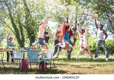 Multiracial friends jumping at barbecue pic nic garden party - Friendship multicultural concept with young happy people having fun dancing out at spring break camp festiva - Bright warm filter