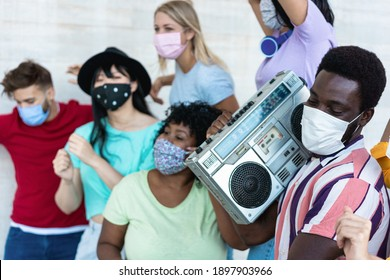 Multiracial friends with masks dancing and listening music with boombox stereo outdoors - Main focus on black man