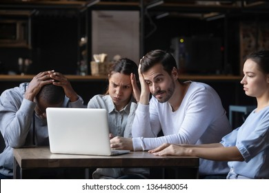 Multiracial friends sitting in cafe bar look at pc screen feels frustrated because of losing online lottery betting loss of money or football fans unsatisfied with referee decision unfair game concept
