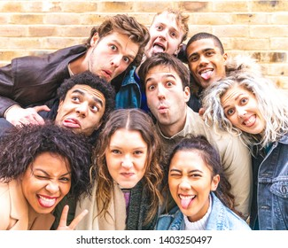 Multiracial friends taking selfie and making funny faces - Group of millennials men and women together in London having fun and enjoying time together - Friendship and millenial lifestyle concepts