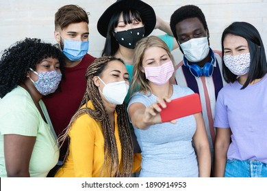 Multiracial friends taking a selfie while wearing masks outdoor - Social distance concept