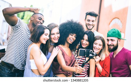 Multiracial friends taking video selfie with mobile phone on stabilized gimbal - Young people having fun on new tech trend - Friendship concept with millenials sharing moment on social media networks