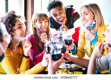 Multiracial friends toasting wine at restaurant bar wearing open face mask - New normal life style concept with happy people having fun together after lockdown reopening - Bright backlight filter