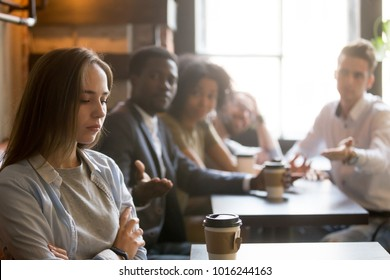 Multiracial friends trying to make peace with insulted girl offended after bad joke, diverse young people apologizing aggrieved resentful drama queen woman sitting apart sulking at meeting in cafe