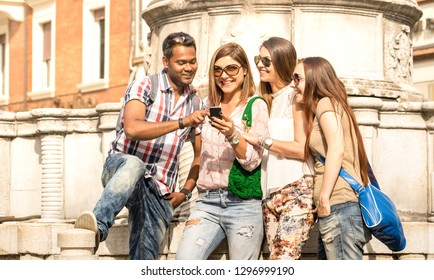 Multiracial friends using mobile smart phone at city tour - Happy friendship concept with student having fun together - Millenial people on peace love concept for no racism - Bright outside filter