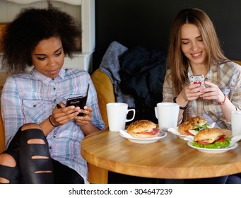 Multiracial girls with cell phones in a cafe