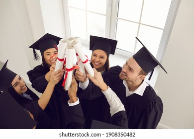 Multiracial graduates raise their diplomas and stack them together by the window in the classroom. Students passed exams, completed a course of study, received a degree. Graduation and people concept.