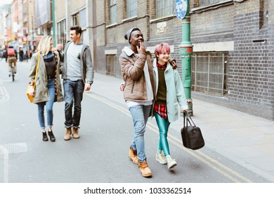 Multiracial Group of Best Student Friends Walking  Outside on the Street and Having Fun Togther. Two Loving Couple Going Arm in Arm Outdoors in the City. Concept of Friendship, Relationship Goals.