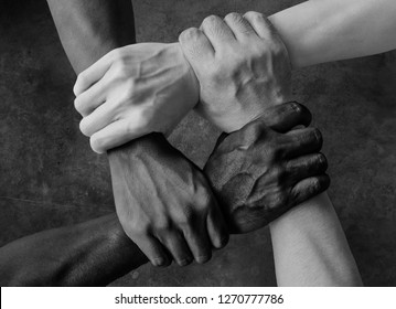 multiracial group with black african American Caucasian and Asian hands holding each other wrist in tolerance unity love and anti racism concept in black and white isolated background