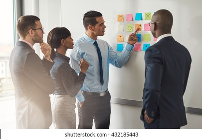 Multiracial group of colleagues discussing a business plan standing around a set of colorful memo notes stuck on the wall