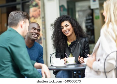 Multiracial group of four friends having a coffee together. Two women and and two men at cafe, talking, laughing and enjoying their time.