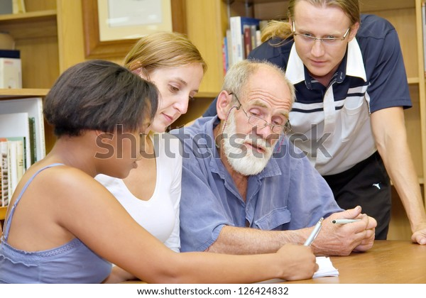 Multiracial group of four people studying in library: African girl explains something to others. Shot in South Africa.
