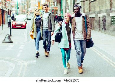 Multiracial group of four people walking on London street and looking at market and shop. Best friends people spending a day trip in European capital. Two couple dating outdoors and making sightseeing