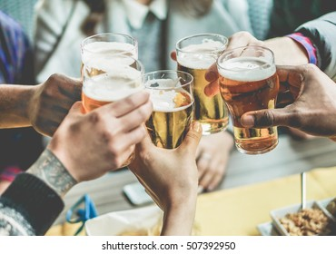 Multiracial group of friends enjoying a beer - Young people hands toasting and cheering aperitif beers half pint - Friendship and youth concept - Warm vintage raw filter - Focus on bottom hand