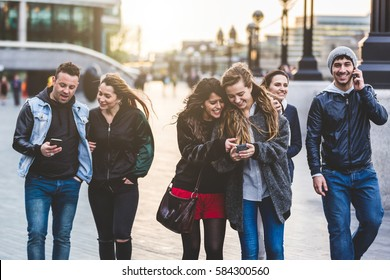 Multiracial group of friends enjoying their time in London. Four women and two men in their twenties, walking and looking at smart phones. Friendship and lifestyle concepts.