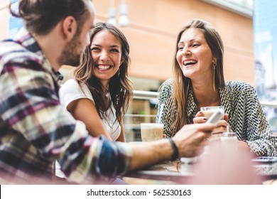 Multiracial group of friends having a coffee together. Two women and a man at cafe, talking, laughing and enjoying their time. Lifestyle and friendship concepts with real people models.