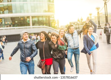 Multiracial group friends having fun in the city at sunset - Happy people in London, boys and girls walking and jumping together - Playful and happy mood, lifestyle situation about friendship