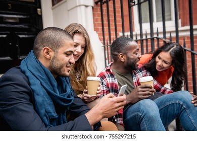 Multiracial group of friends having fun together in London. Two girls and two boys, talking and laughing. Residential district with houses and cars on background. Lifestyle and friendship concepts.