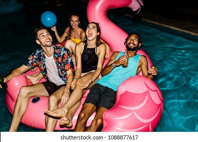 Multiracial group of friends having party in a swimming pool. Happy young people chilling on air mattress in pool.