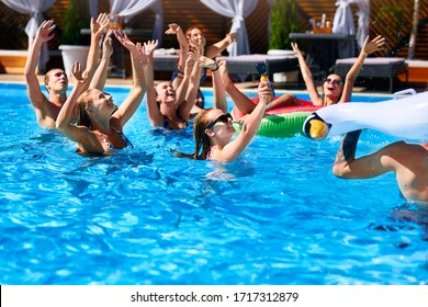 Multiracial group of friends having party in private villa swimming pool. Happy young people in swimwear dancing and splashing with inflatable floaties at luxury resort on sunny day. Girls in bikini.