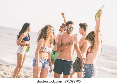 Multiracial group of friends having a party on the beach, dancing and drinking beer. They are teenagers, four girls and three boys, standing just next to the seaside.