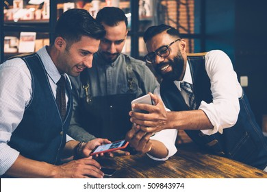 Multiracial group of friends looking at phone screen with smile at table