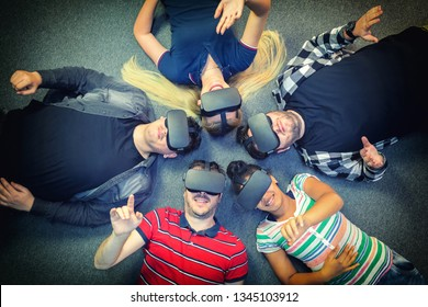 Multiracial group of friends playing on vr glasses indoor - Virtual reality concept with young people having fun together connecting with headset goggles. Digital generation trends