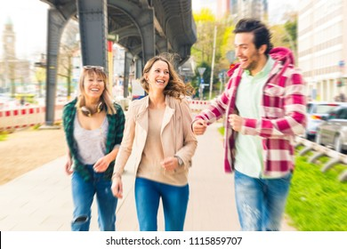 Multiracial group of friends running and having fun in Hamburg. Two women and a man enjoying their time together in the city. Friendship and lifestyle concepts.